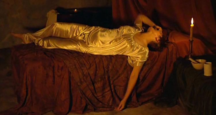"""scène du film d'Eric Rohmer """"Die Marquise von O..."""", d'après la nouvelle de Kleist: la marquise, en pyjama de soie, est allongée sur un lit avec des draps rouges sombres, son bras pend en-dehors du lit et elle recouvre son visage de sa main"""