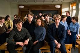 Affiche pour film la révolution silencieuse de Lars Kraume des lycéens sont assis sur leur table dans une salle de classe et regardent le photographe droit dans les yeux