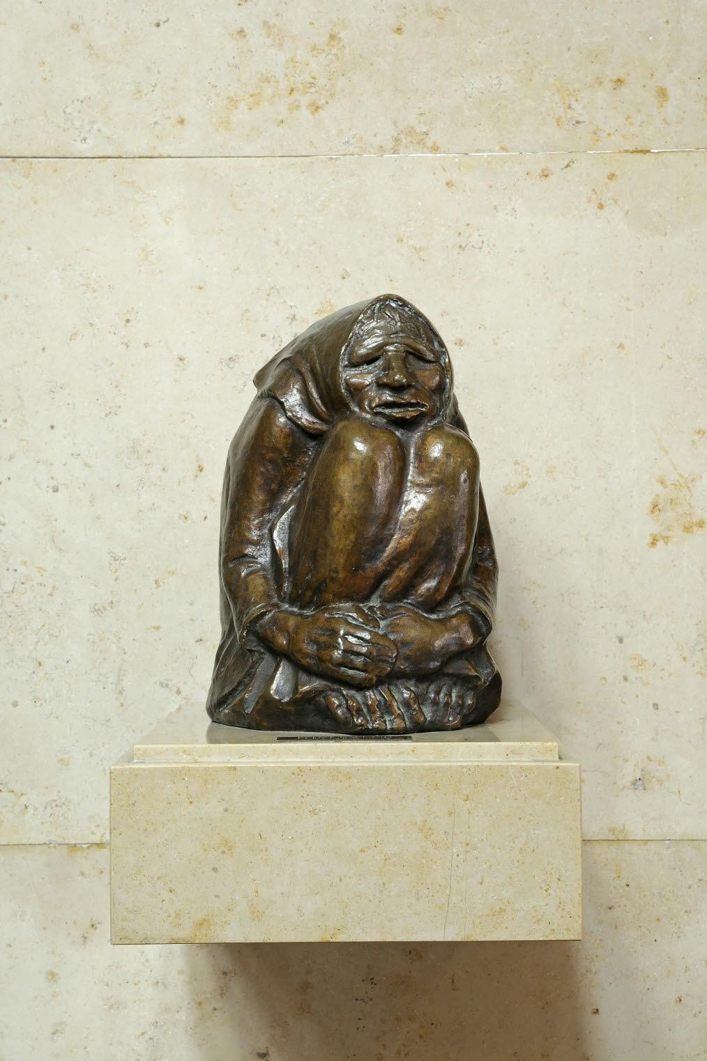 """Statue en bronze """"Frierende Alte""""  d'Ernst Barlach, l'original de 1937 est en teck, représentant une vieille femme coiffée d'un fichu, recroquevillée sur elle-même, accablée par le froid"""