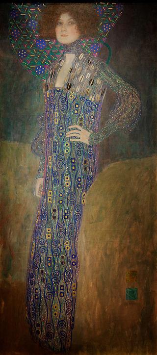L'amante de Klimt regarde fièrement le spectateur, debout un poing sur la hanche. Elle est vêtue d'une longue robe bleue à motifs stylisés et se tient devant un fond très simple de noir et d'or, sur lequel se détachent quelques fleurs bleues géométriques.