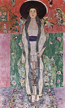 Une femme au grand chapeau noir se tient debout, statique, et nous regarde. Ses vêtements sont simples, symétriques de droite à gauche. Au fond, des motifs asiatiques rouges et verts et un draps représentant des fleurs contrastent fortement.