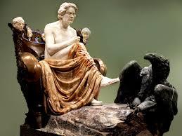 Die statue besteht aus verschiedenen Marmorarten. Beethoven sitzt auf einem Thron und denkt nach. An seinen Füssen ist ein schwarzer adler, der ihn anschaut.