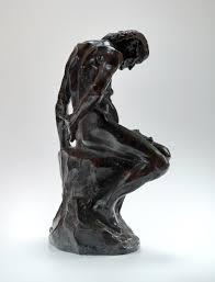 La sculpture est noire et brillante. Une vielle femme se tient assise et recroquevillée, les mains dans le dos. Ses os paraissent à travers sa peau.
