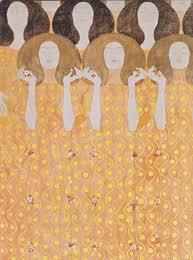 Des femmes toutes semblables se tiennent par les mains pour chanter. Elles ferment les yeux. Leur robe orangée oscile dans la musique.