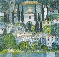 Eine Kirche ud ein Dorf überragen ein See. Es sind viele Zypresse zu sehen, die sich in dem See spiegeln. Alles ist grün und blau.