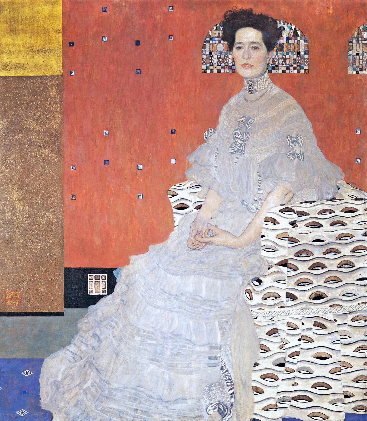 Une femme vêtue de blanc est assise sur un fauteuil blanc orné de motifs bruns. Le fond est très simple, un applas de couleur rouge et or. Derrière ses cheveux, les motifs du fond dessines une coiffe de l'ancien temps. Elle est songeuse, ses mains se tordent. Elle est pâle et a la bouche entre-ouverte.
