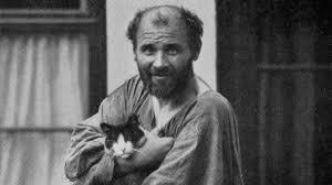 Klimt regarde le photographe avec bonhomie. Il tient dans ses bras un chat qui regarde également le photographe. Le peintre a le front dégarni, il porte un ample tablier.