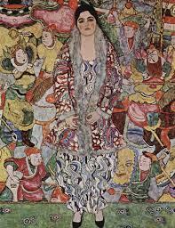 Eine Frau steht im langen, bunten Pelzmantel. Ihre Hose ist orientalisch. Im Hintergrund sind viele bunte Figuren auf der Wand gemalt. Es sind Drachen, Könige, Bauer, alles im asiatischen Stil.