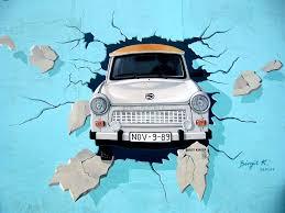 fresque peinte sur le mur de Berlin représentant une Trabant traversant le mur