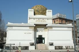 Sur la photo on voit le palais de la Secession. Ce bâtiment est très clair et fait de formes rectangulaires, mis à part la grande sphère sur le toit qui est faite de fleuilles dorées.