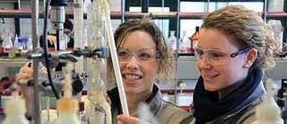 Photo représentant 2 jeunes filles souriantes en train d'expérimenter dans un laboratoire